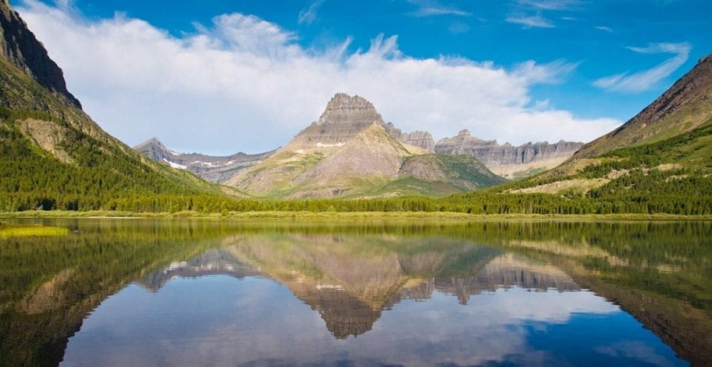 Mountains are reflected over Two Medicine Lake in Glacier National Park