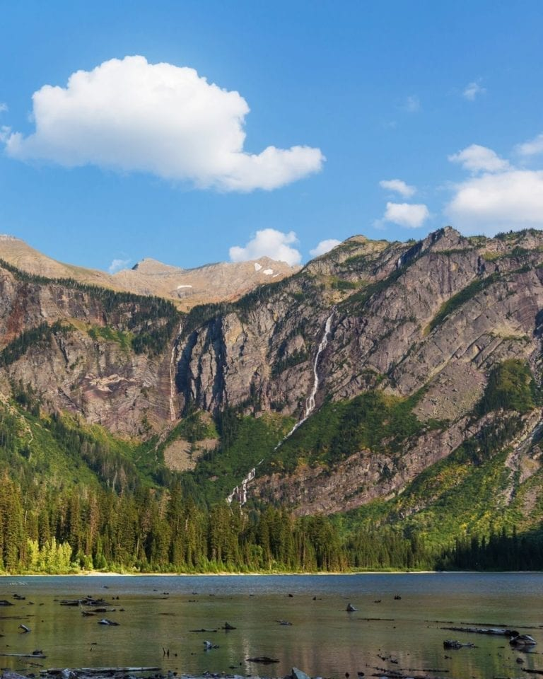 Avalanche Lake in the forefront of avalanche chutes on the mountainside in Glacier National Park
