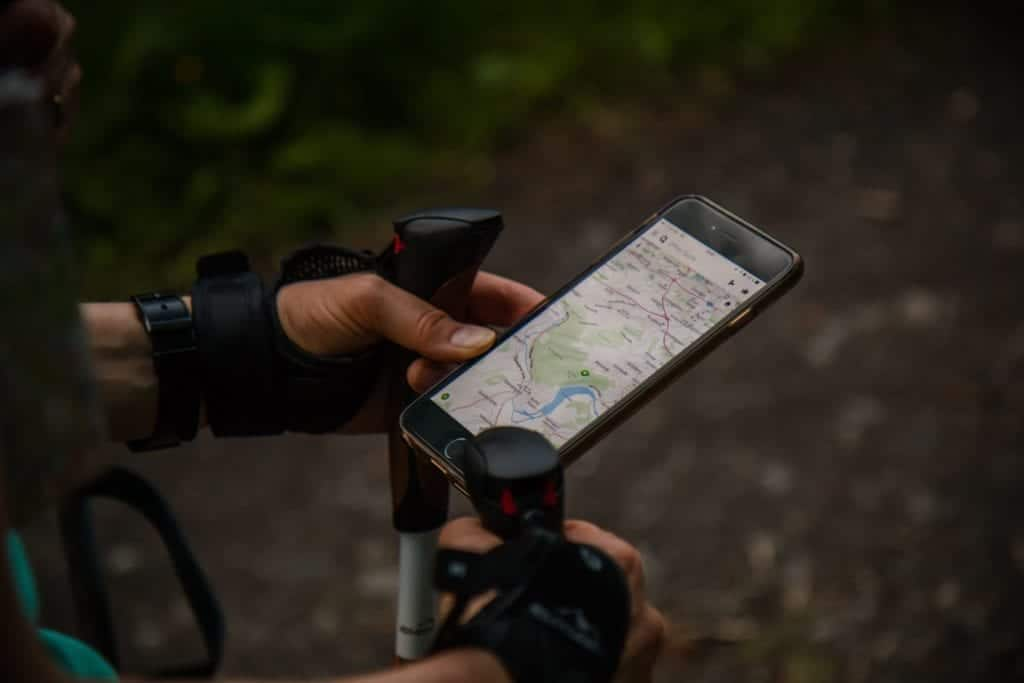 Hiker uses map on smartphone with trekking poles