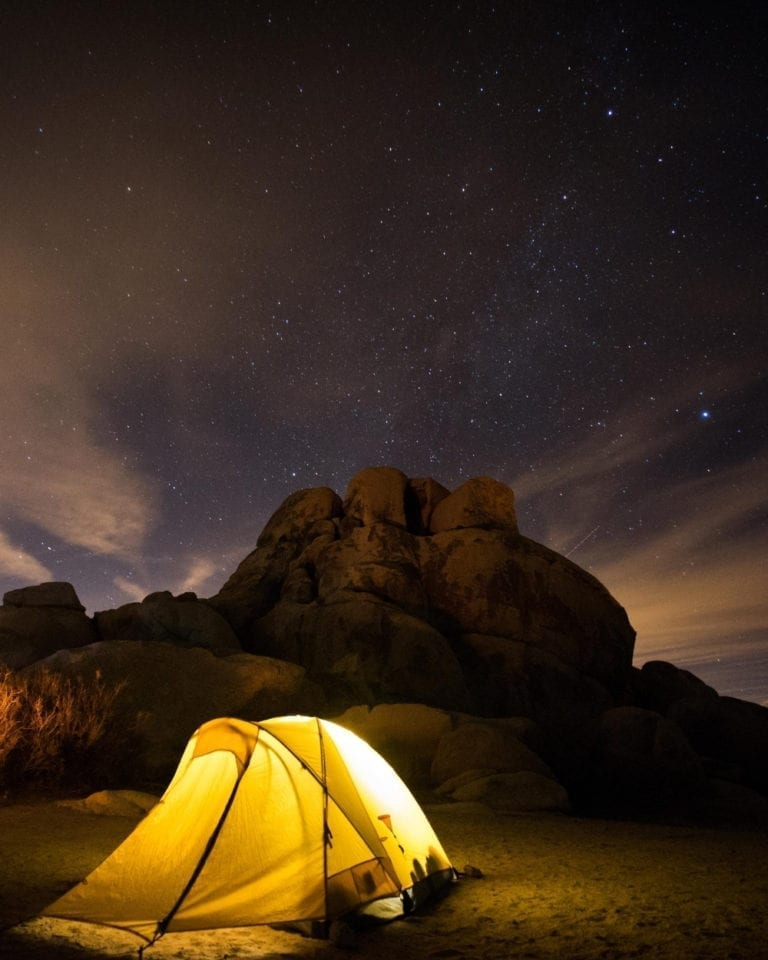 A tent glows in the dark night skies of Joshua Tree National Park