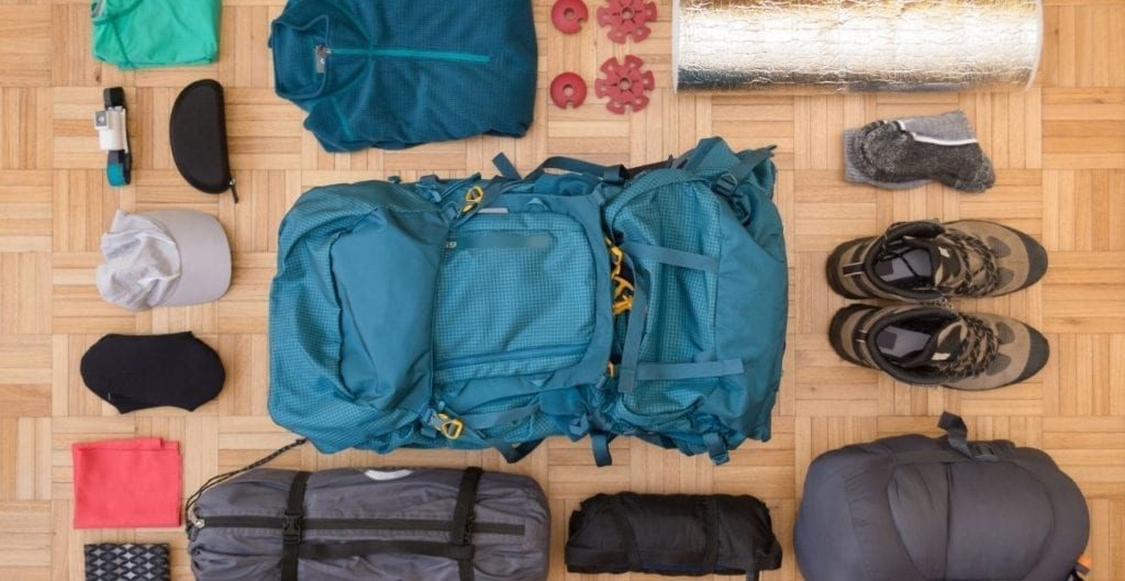 Hiking and camping gear laid out on floor.