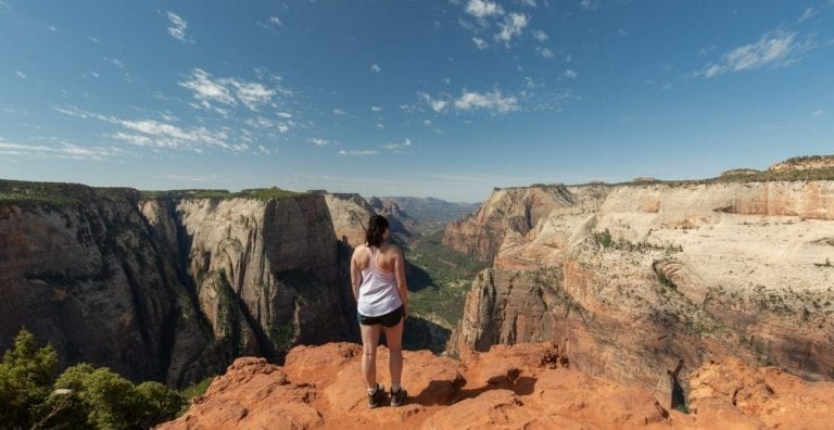 A hiker stands at Observation Point overlooking Zion Canyon in Zion National Park