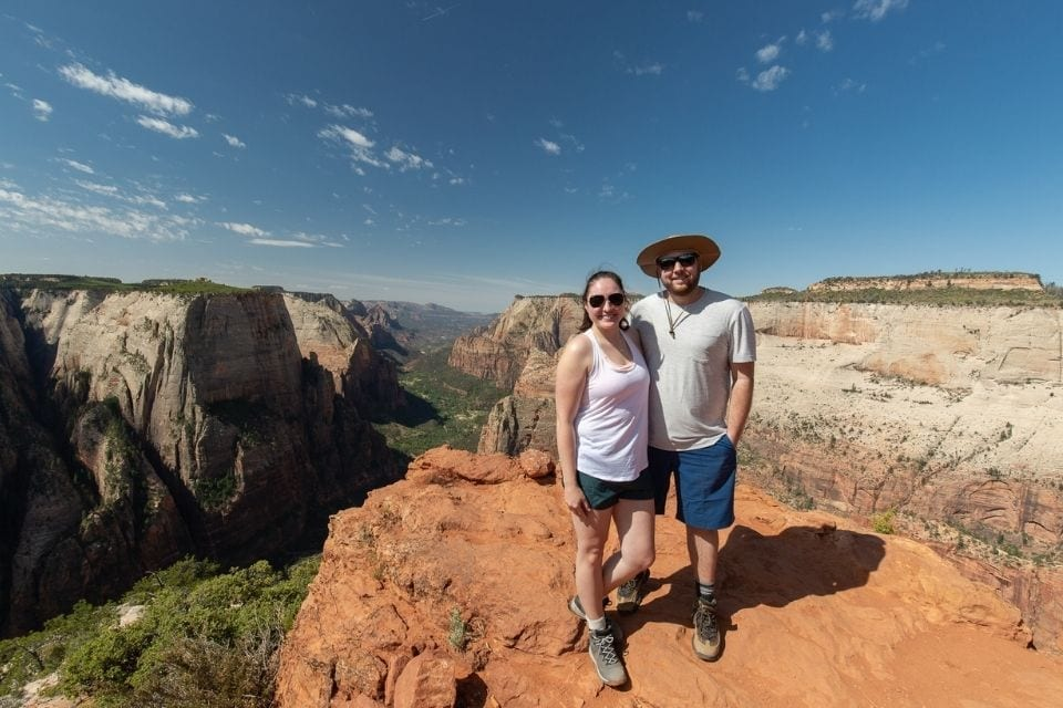 A couple stands atop Observation Point in Zion National Park overlooking Zion Canyon.