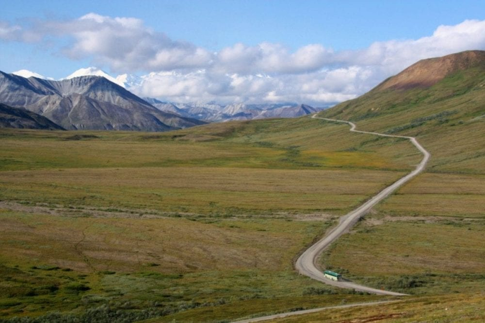 A long road way leads through a green valley between tall Alaskan mountains on a road trip through the Alaskan Frontier