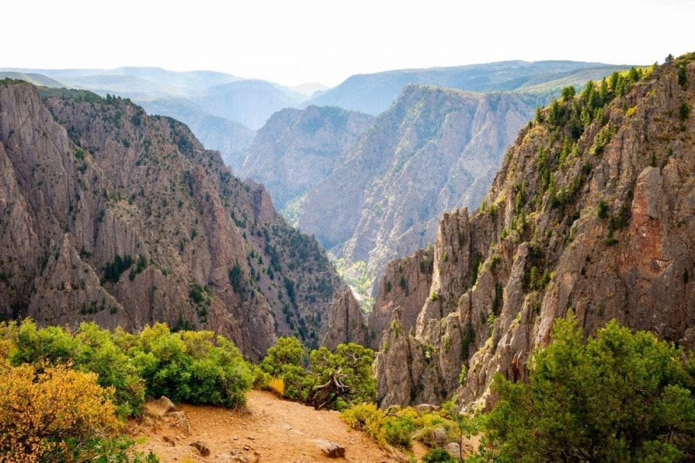 The Gunnison River splits the mountains in two across the long valley in Black Canyon of the Gunnison National Park in Colorado