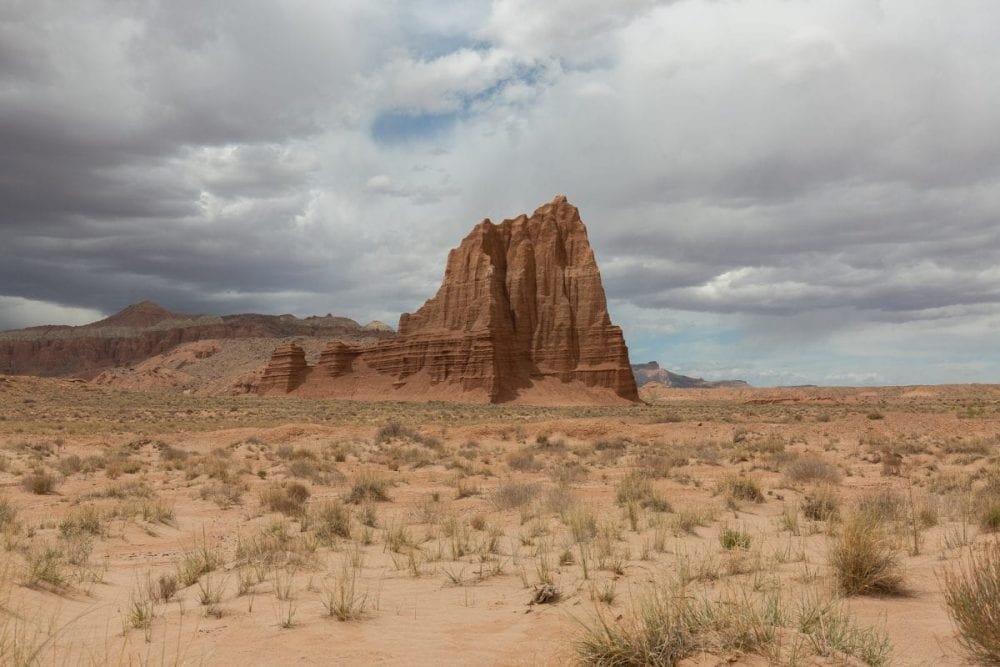The single jagged rock, Temple of the Sun, stands tall in the desert in Capitol Reef National Park in Utah