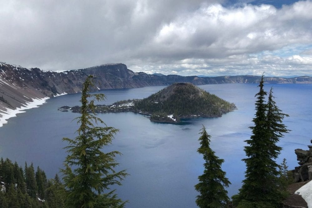 A lone island sits in the middle of the dark blue Crater Lake in Oregon.