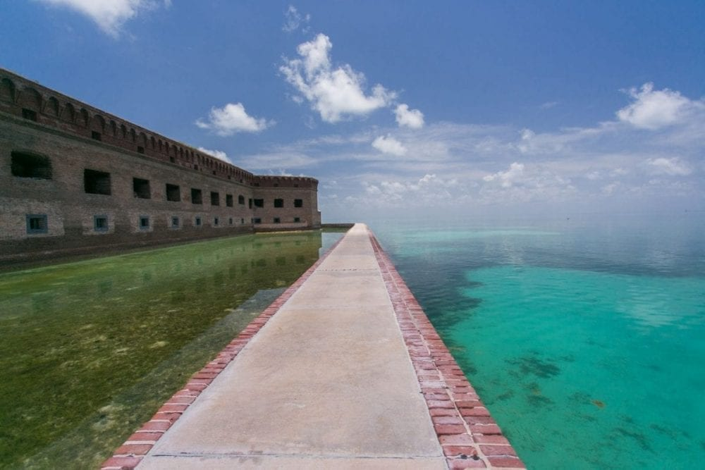 A long concrete and brick boardwalk runs next to Fort Jefferson along the ocean in Dry Tortugas National Park in Florida