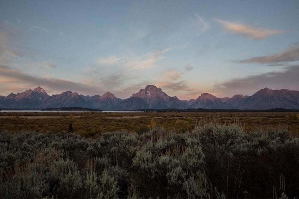 The distant Teton Mountains glow in the pink and orange sunset in Grand Teton National Park in Wyoming