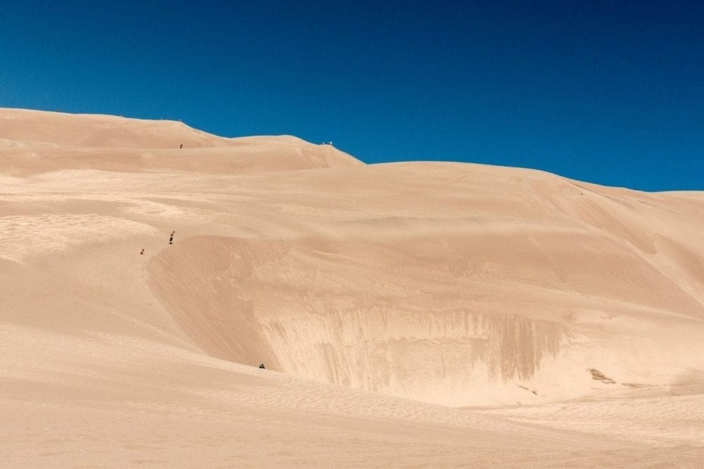 Hikers trek across giant, beige sand dunes in Great Sand Dunes National Park in Colorado
