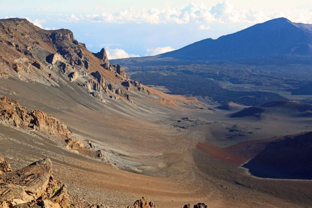 Brown dirt covers sloping mountains in the barren area of Haleakala National Park in Hawaii