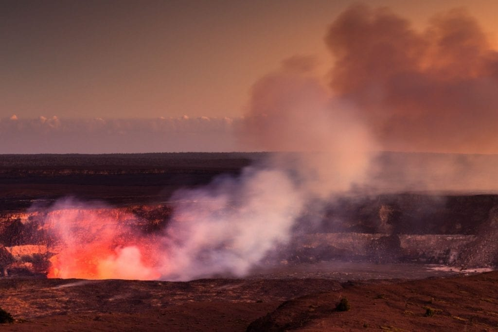 Bright red lava and steam releases from the crater in Hawaii Volcanoes National Park in Hawaii