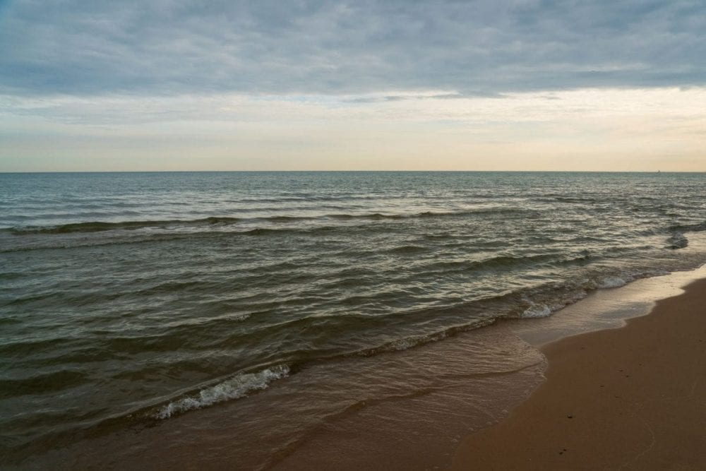 Small waves crash on the sandy beach shore at Indiana Dunes National Park in Indiana