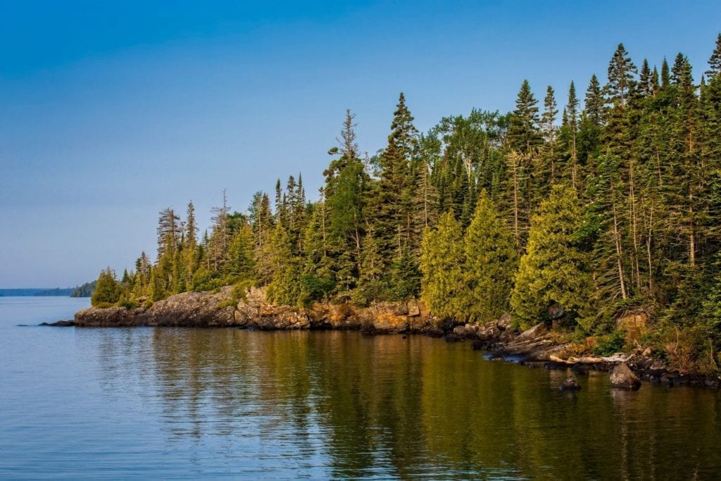 Pine trees sit along the rocky shore lines of the lake island at Isle Royale National Park in Michigan