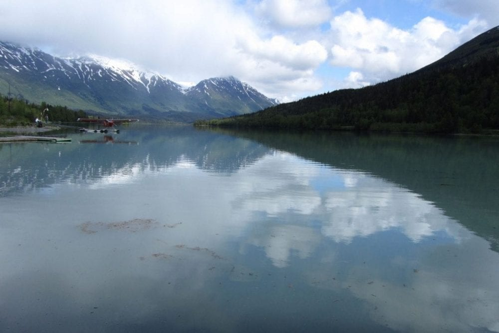 A mountain is reflected in a glassy lake in Kenai Fjords National Park in Alaska