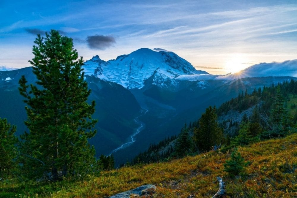The sun sets behind a snow covered Mount Rainier in the distance in Mount Rainier National Park in Washington
