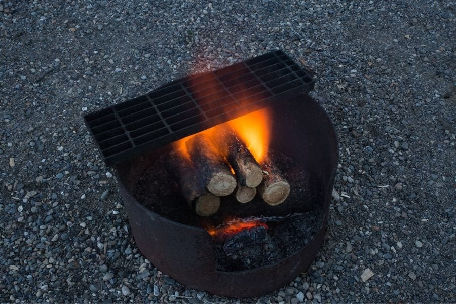 A wood fire burns in a campfire pit and grill in a campground