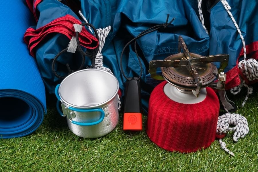 Camping gear is laid on on the grass preparing for a first camping trip.