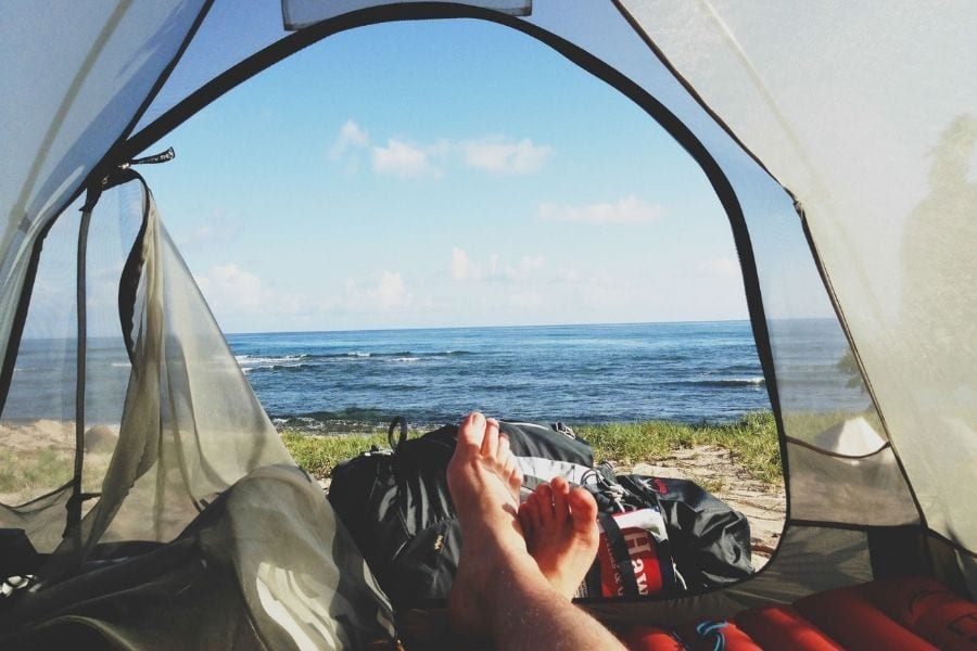 A camper lays in their tent facing out towards the ocean