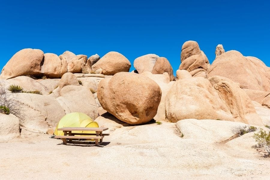A yellow tent at a campsite in Jumbo Rocks Campground in Joshua Tree
